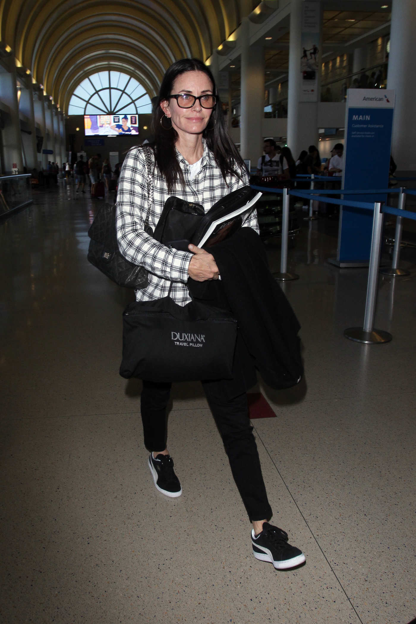 Courteney Cox in a Black Puma Sneakers Arrives at LAX Airport in Los Angeles 10/20/2018