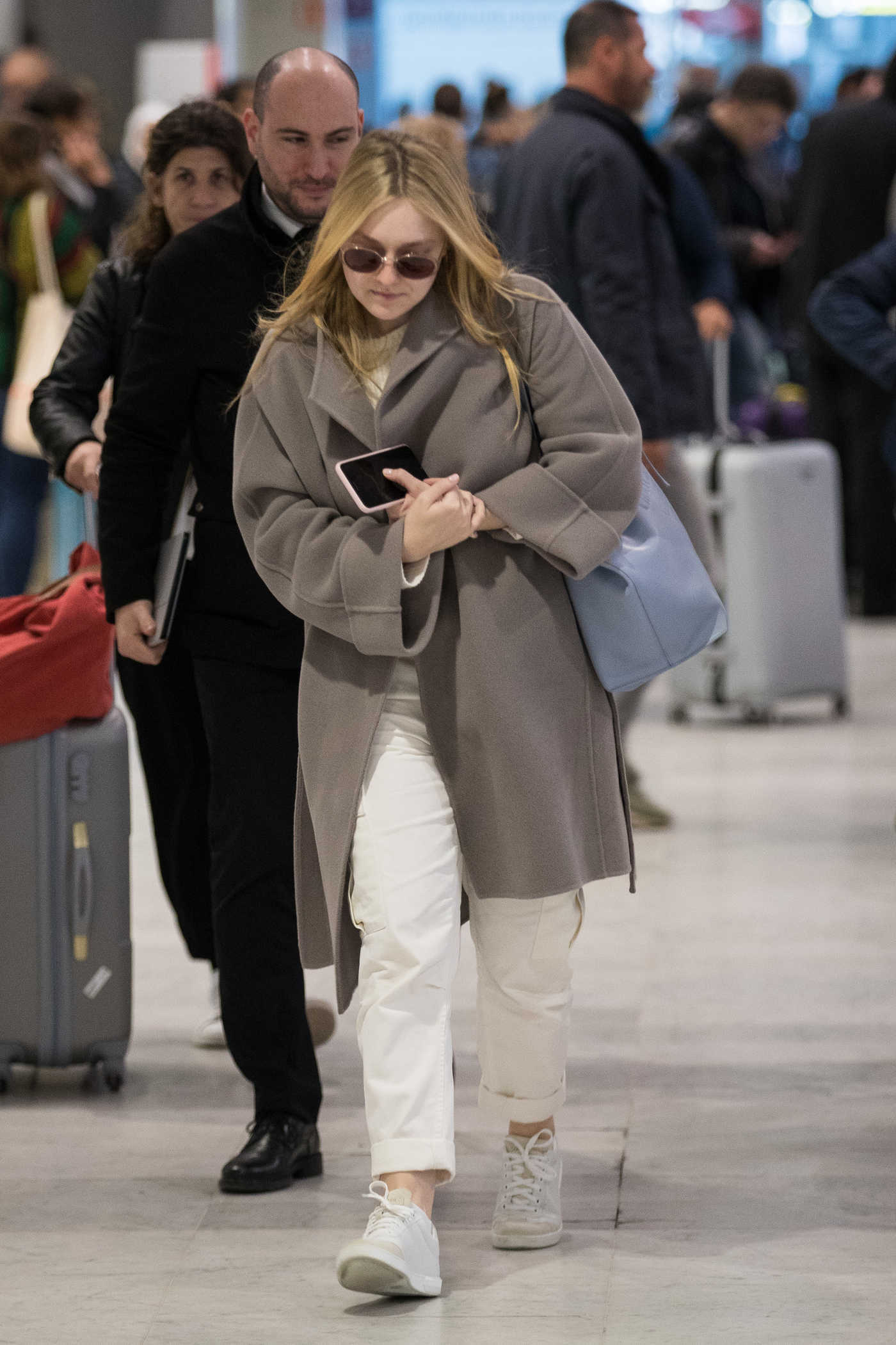 Dakota Fanning in a Beige Coat Arrives at the CDG Airport in Paris 01/21/2019