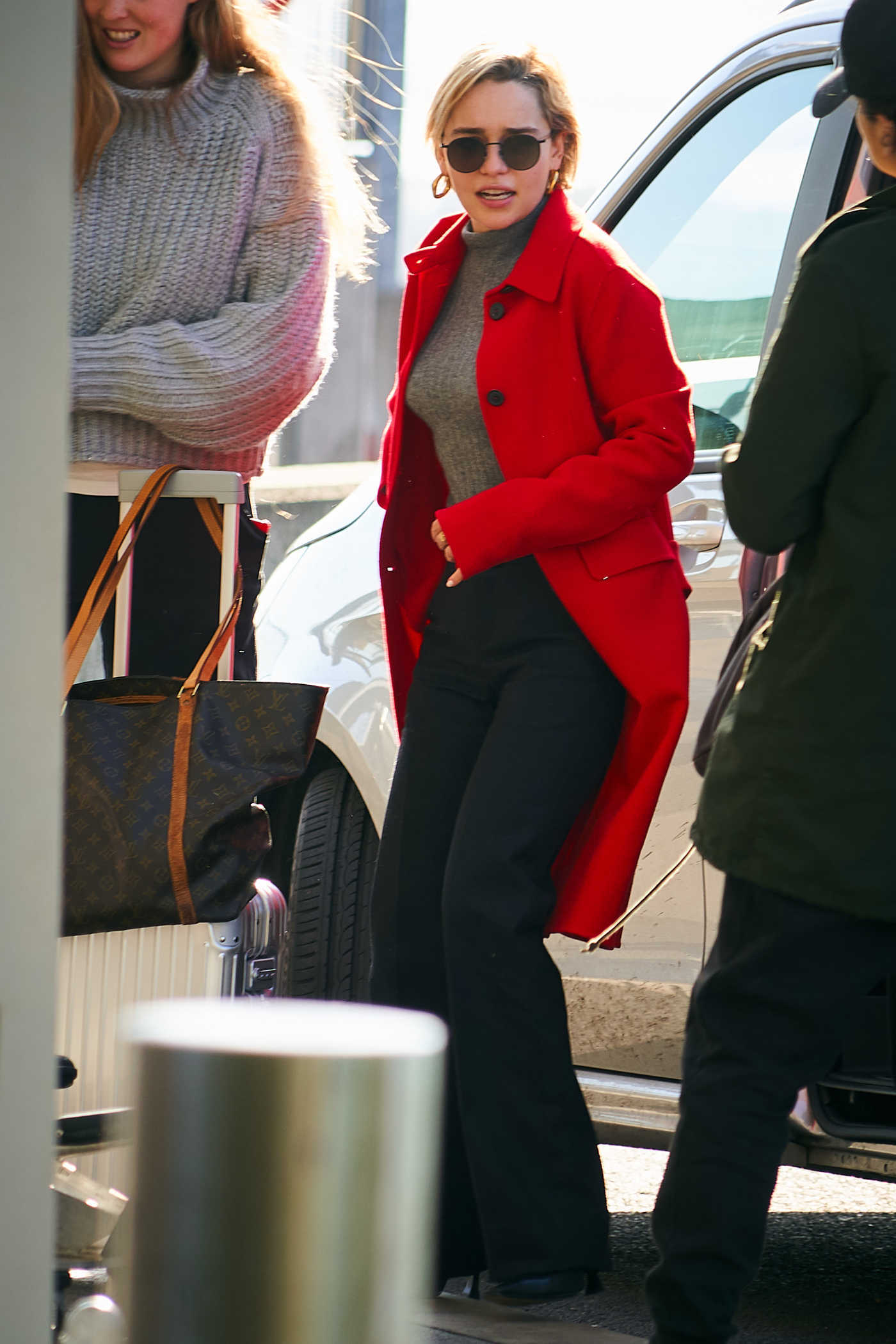 Emilia Clarke in a Red Coat Arrives at Heathrow Airport in London 02/21/2019