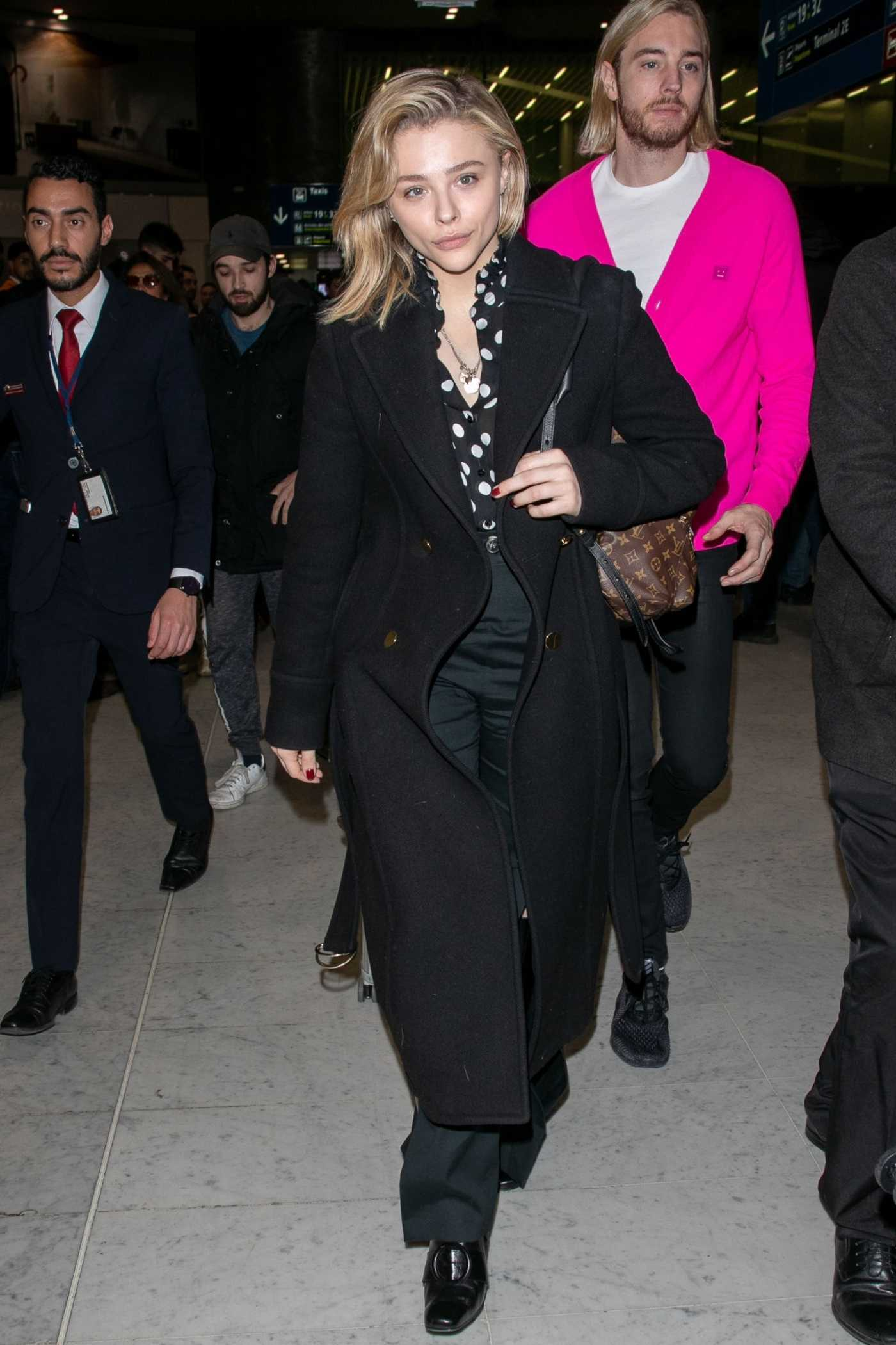 Chloe Moretz in a Black Coat Arrives at the CDG Airport in Paris 03/03/2019