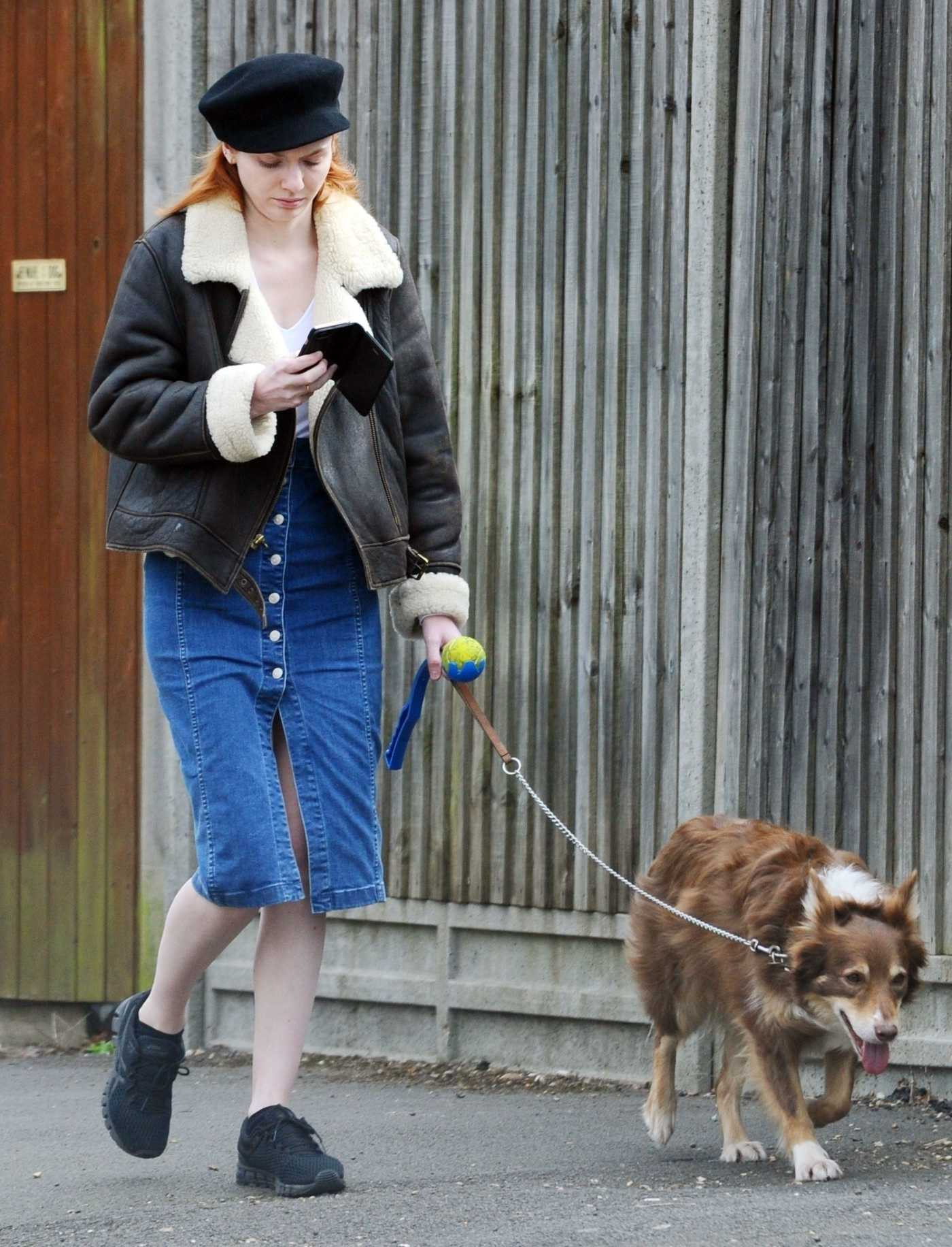 Eleanor Tomlinson in a Black Cap Was Seen Out with Her Dog in the Park in London 03/29/2019