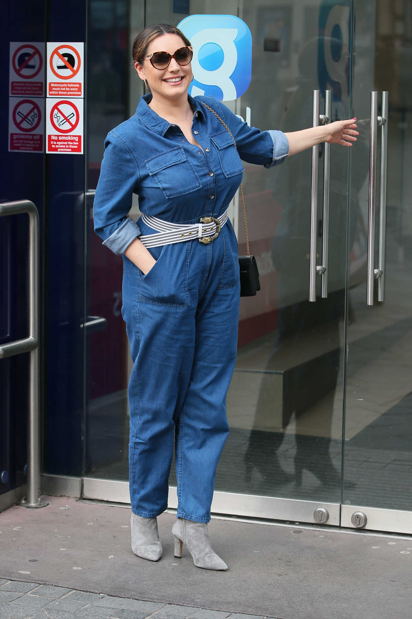 Kelly Brook in a Blue Denim Overalls Arrives at Global Radio Studios in London 03/05/2019