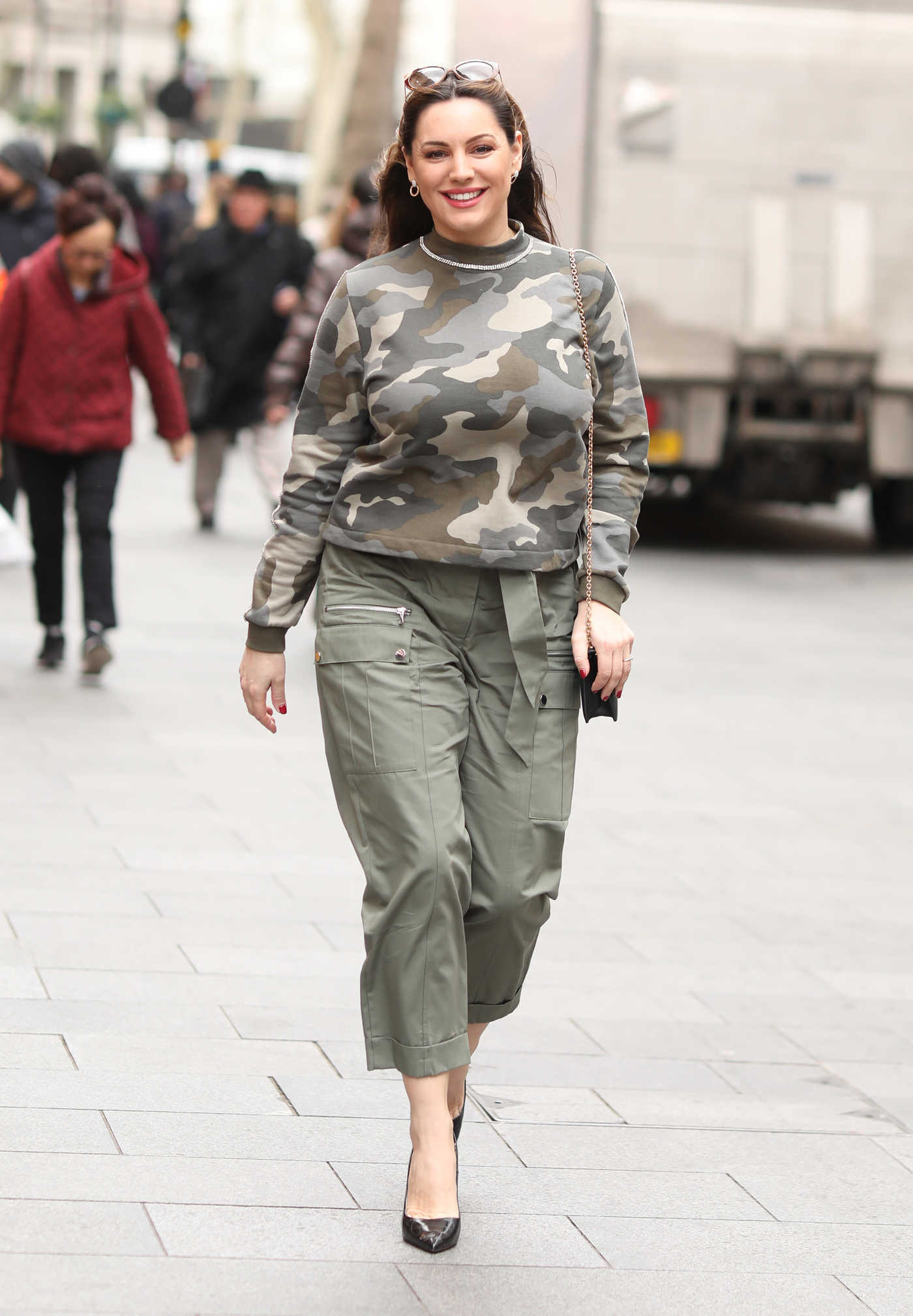 Kelly Brook in a Camo Sweatshirt Arrives at Global Radio Studios in London 03/13/2019
