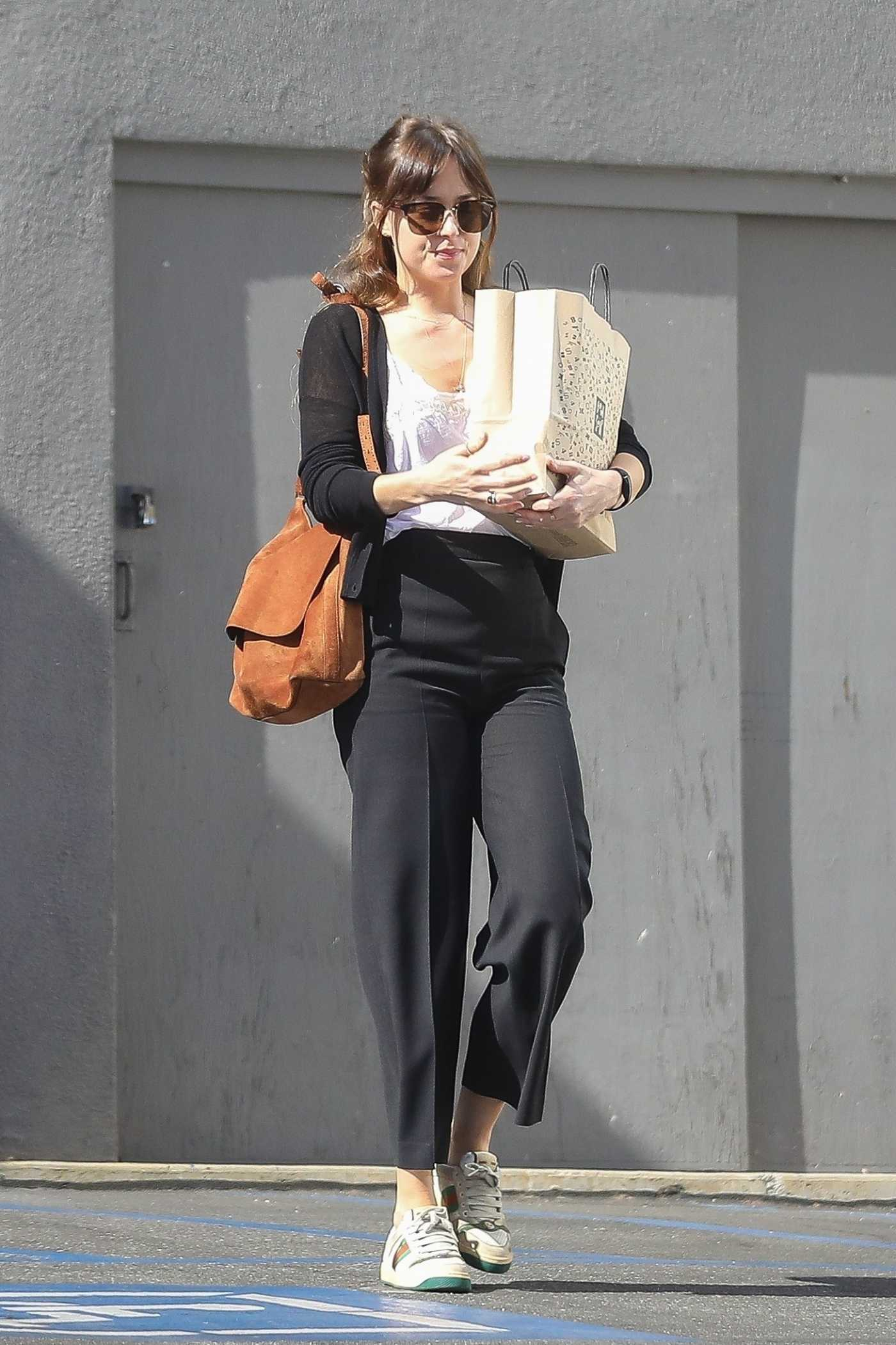 Dakota Johnson in a Black Pants Goes  Shopping in West Hollywood 04/24/2019