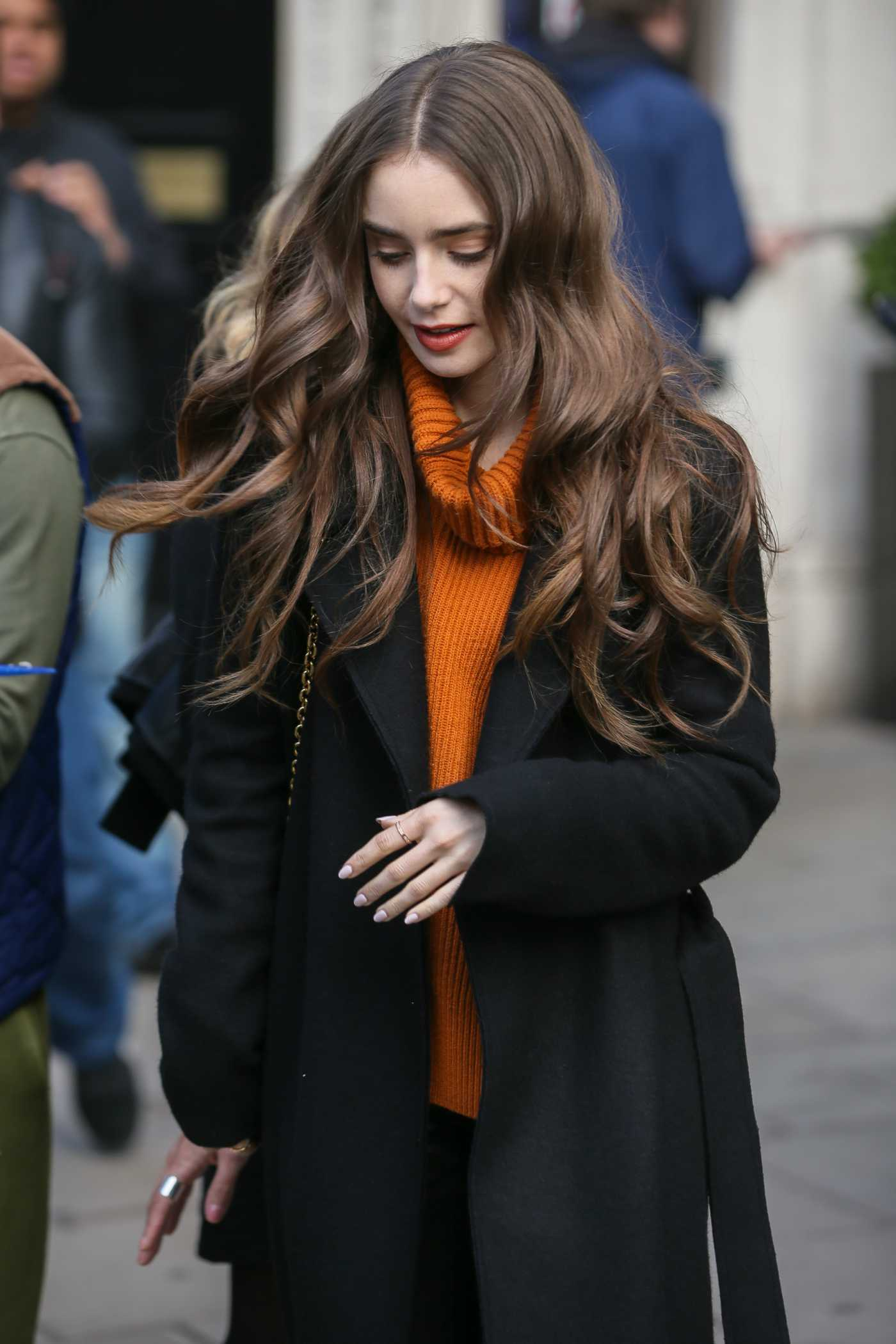 Lily Collins in an Orange Sweater Arrives at Kiss Radio Studios in London 04/29/2019