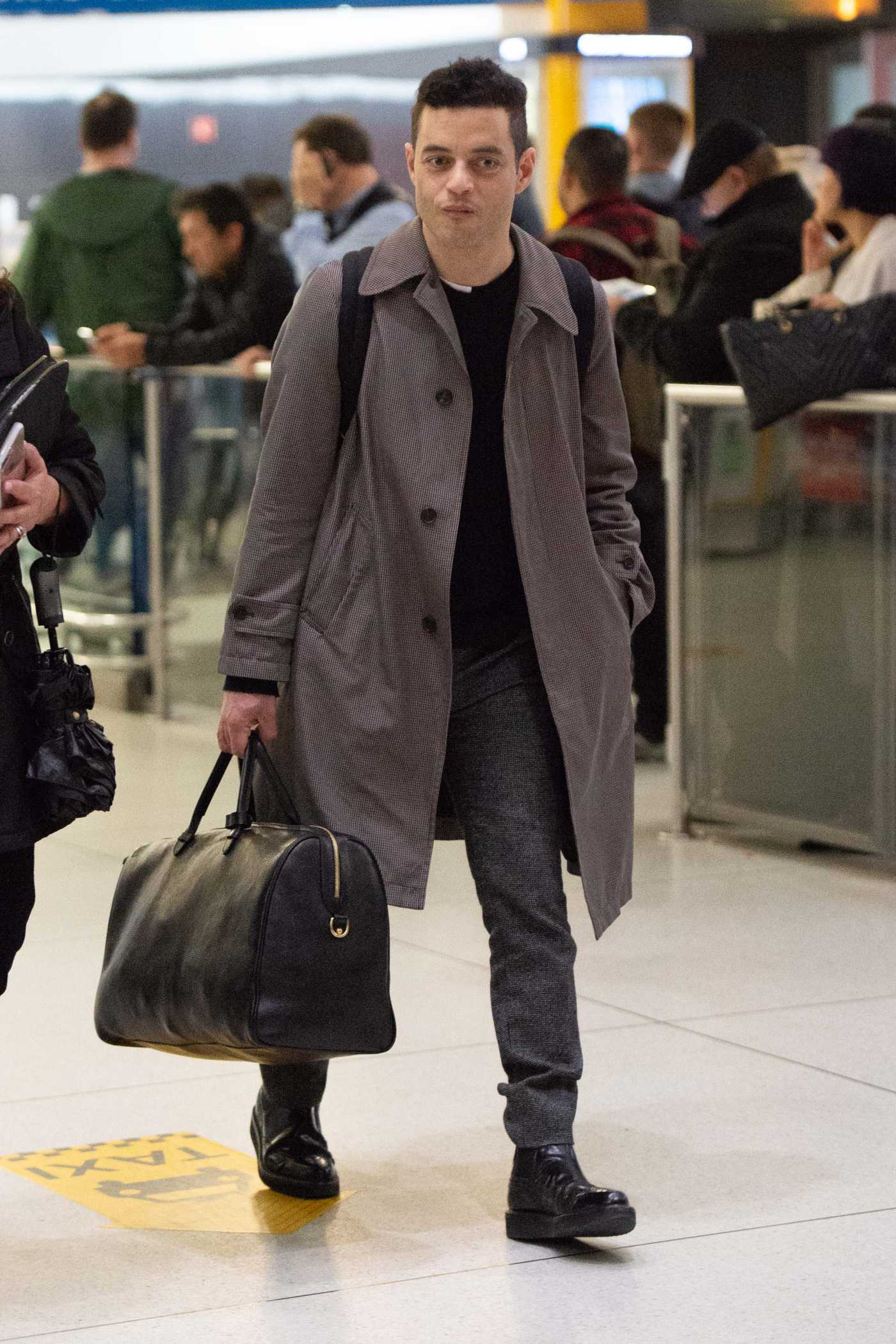 Rami Malek in a Beige Trench Coat Arrives at JFK Airport in NYC 04/13/2019