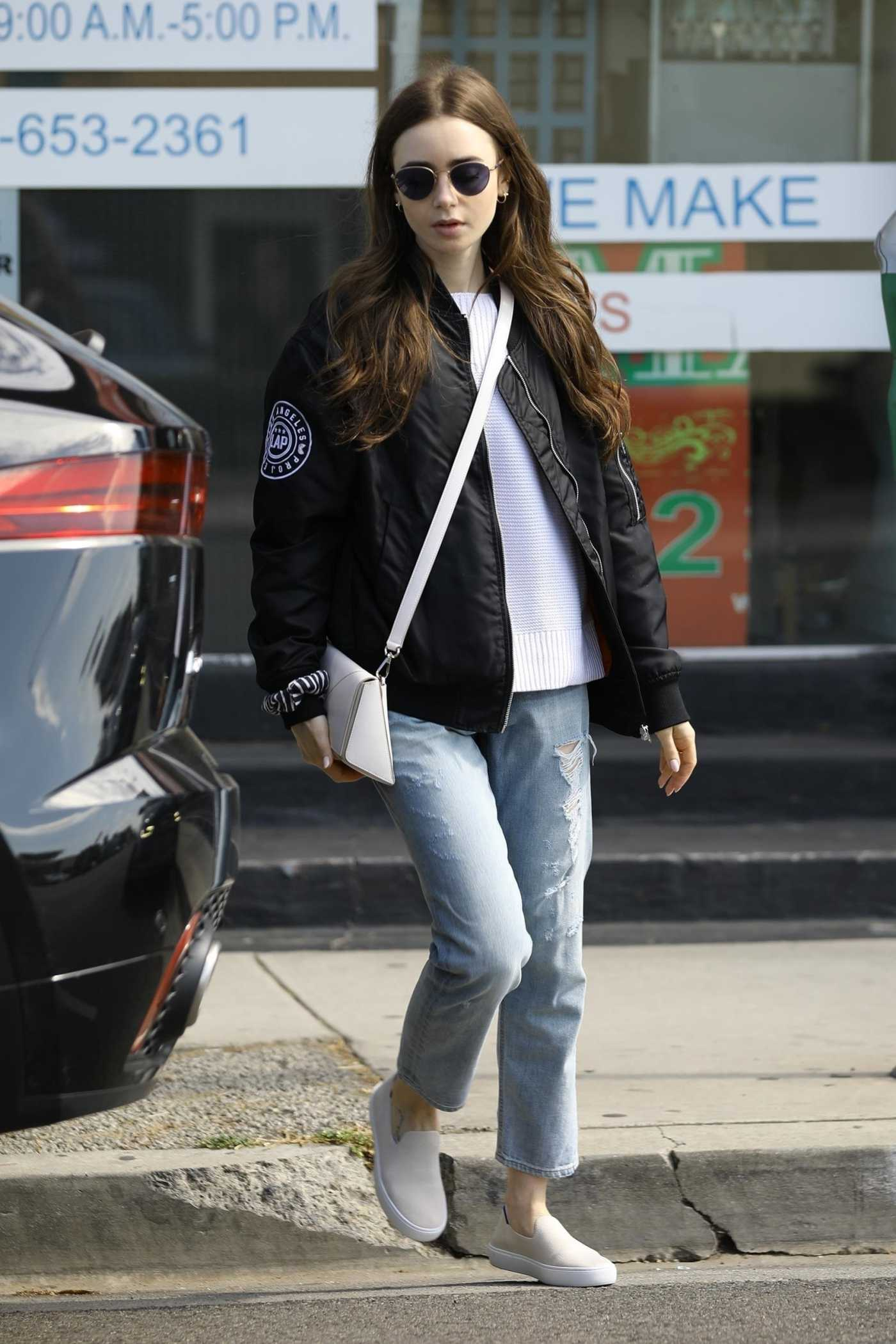 Lily Collins in a Blue Ripped Jeans Picking up Some Dry Cleaning in Los Angeles 05/11/2019