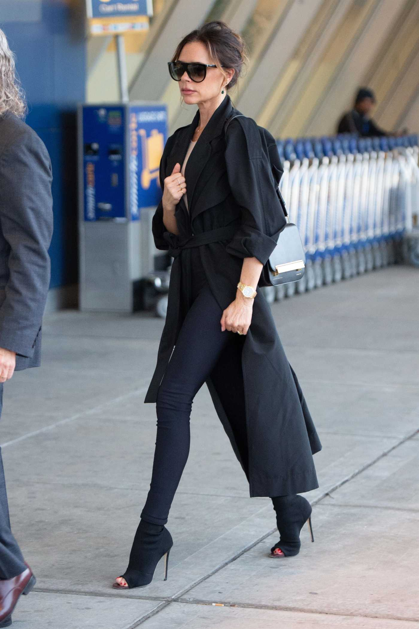 Victoria Beckham in a Black Trench Coat Arrives at JFK Airport in NYC 05/11/2019