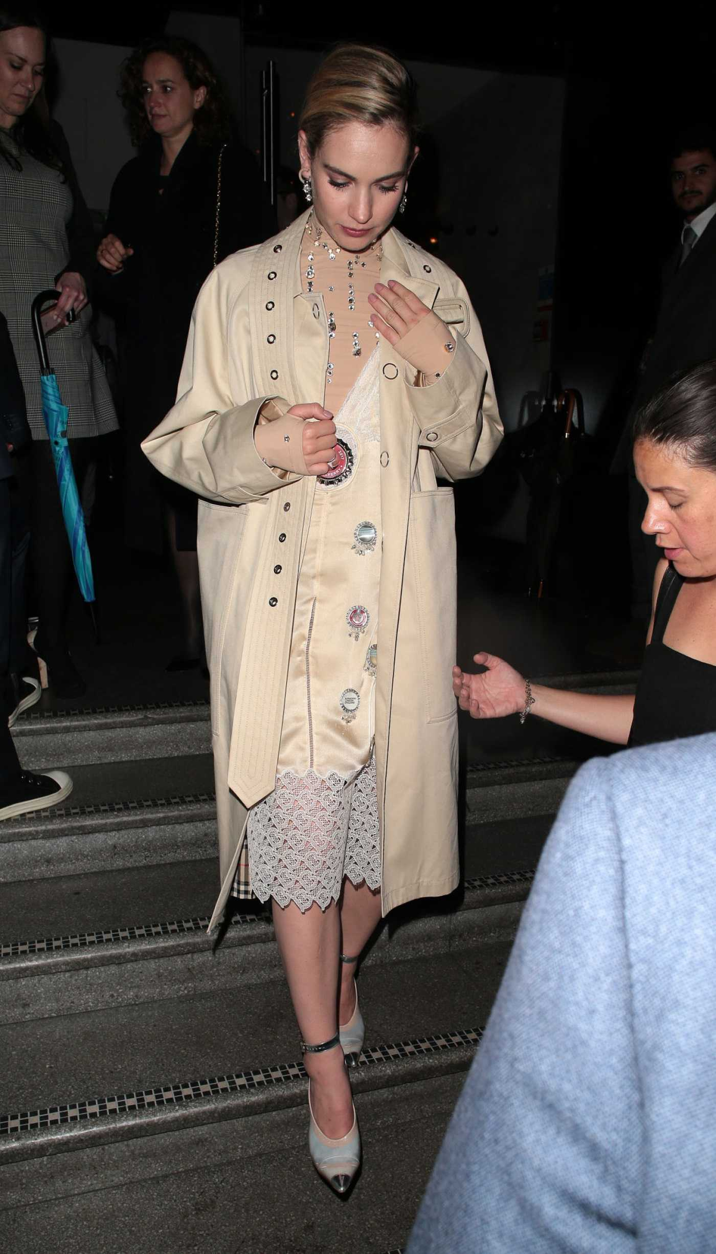 Lily James in a Beige Trench Coat Arrives at Yesterday Afterparty at 100 Wardour Street in London 06/18/2019