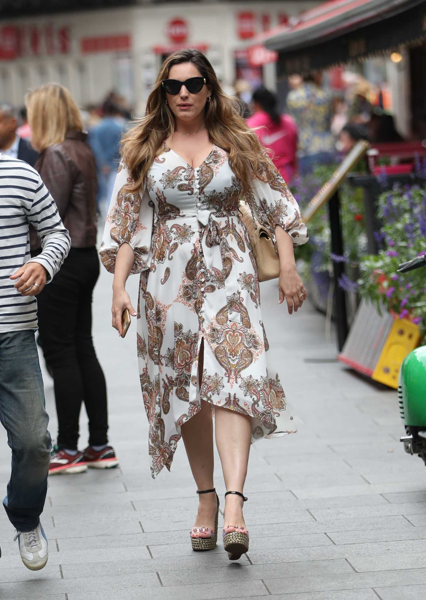 Kelly Brook in a White Floral Dress Arrives at Global Radio Studios in London 07/15/2019