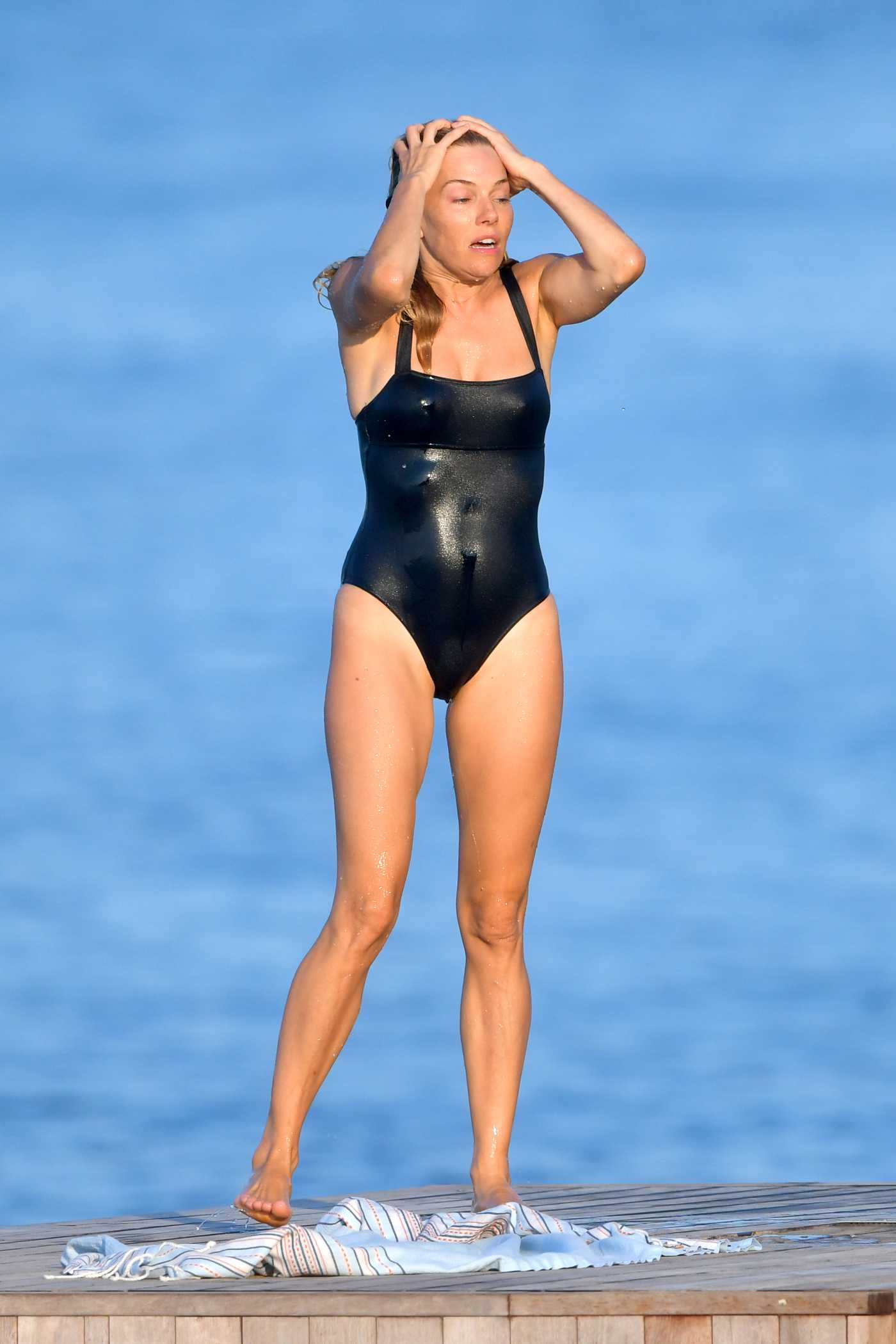 Sienna Miller in a Black Swimsuit on the Beach in St Tropez 08/08/2019