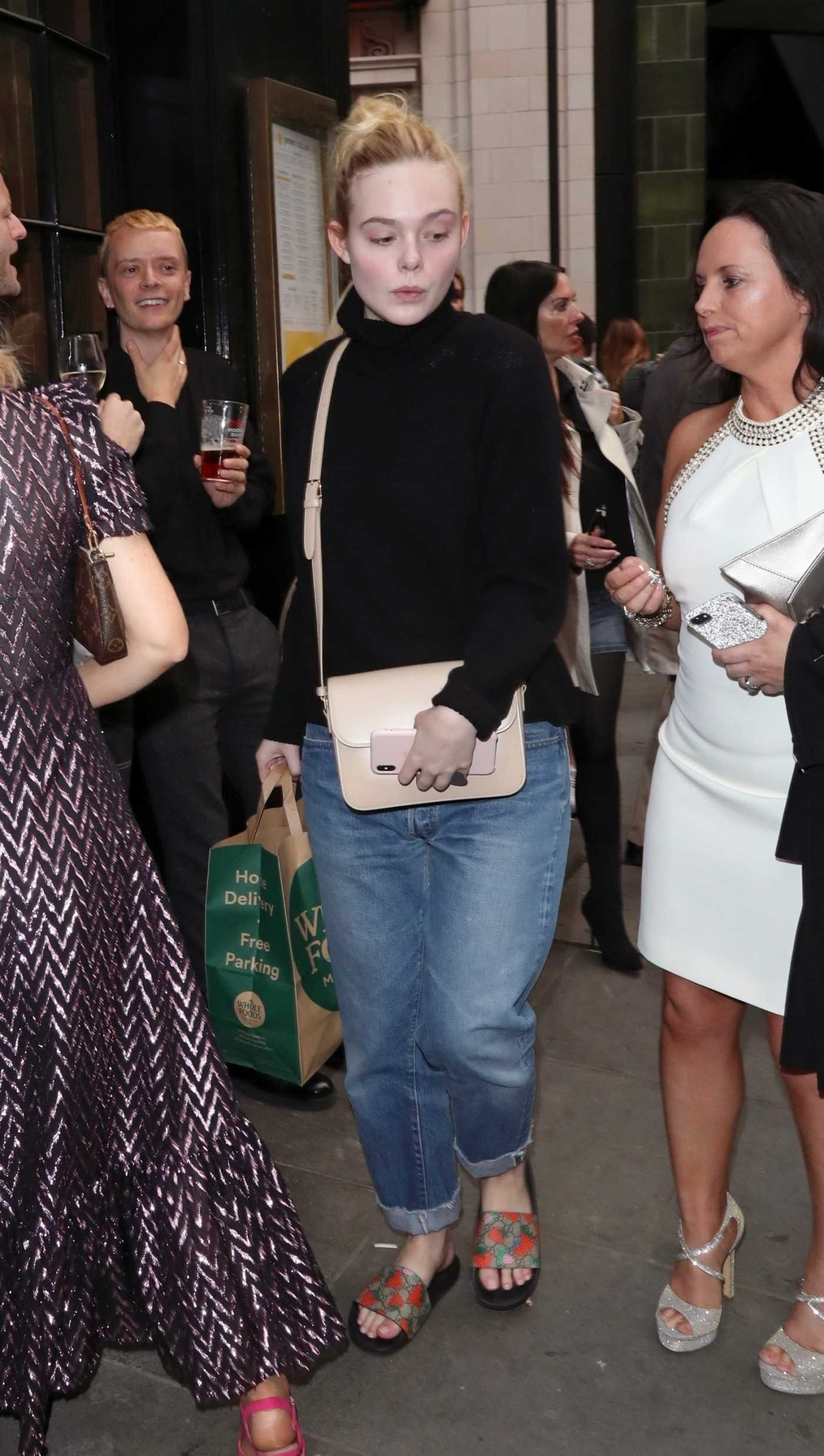 Elle Fanning in a Black Turtleneck Out Carrying a Whole Foods Grocery Bag in Soho, London 09/11/2019