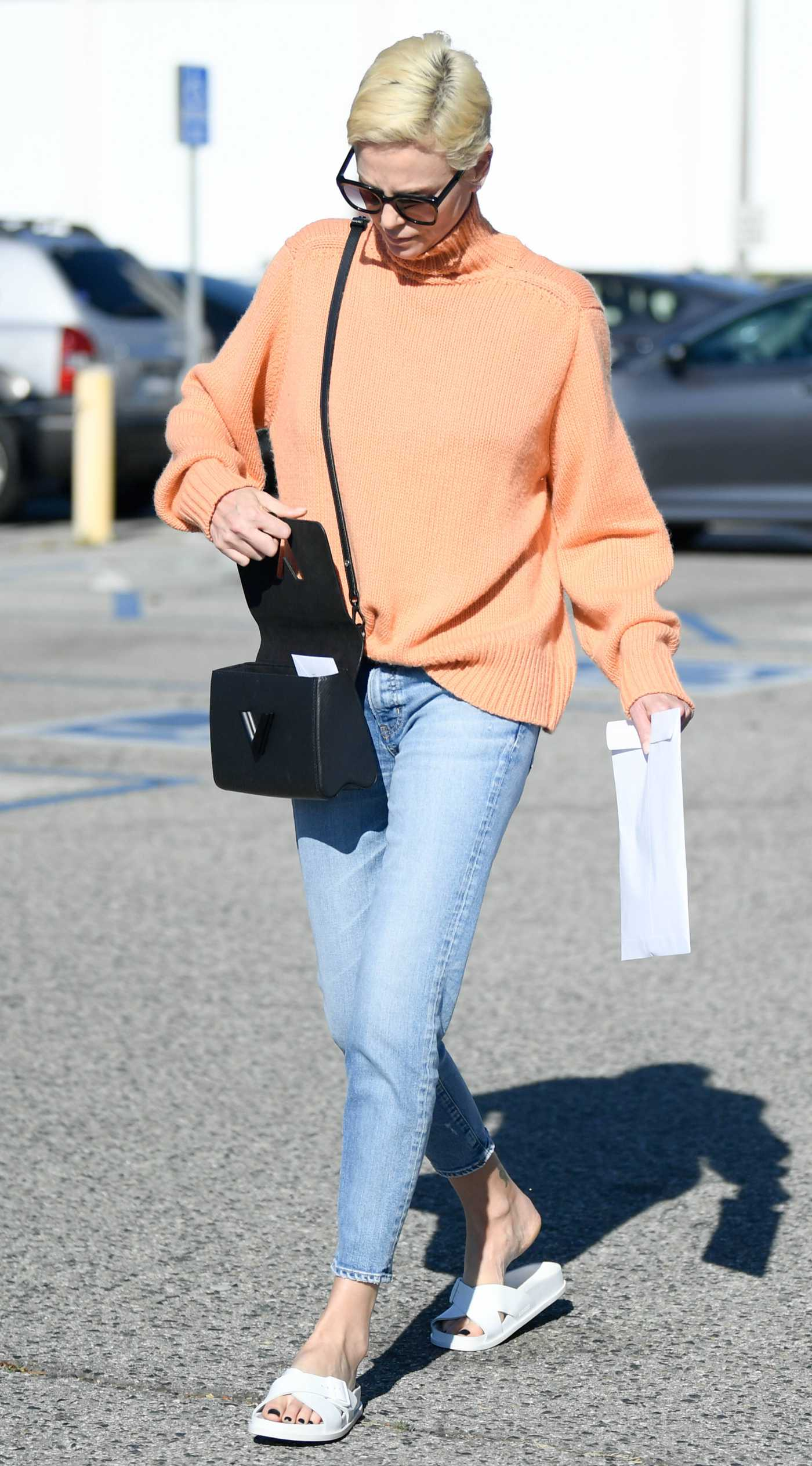 Charlize Theron in an Orange Sweater Leaves the West LA Federal Building in Los Angeles 02/25/2020
