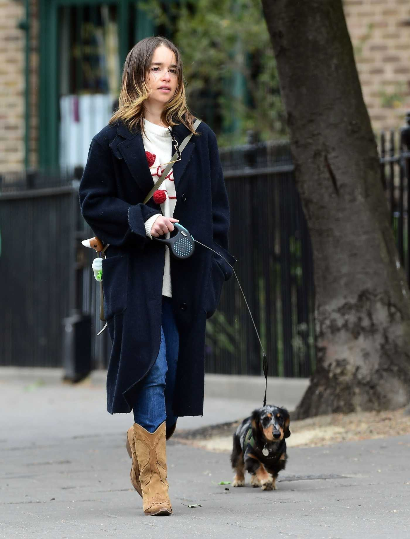 Emilia Clarke in a Black Coat Walks Her Dachshund Dog at the Park in London 06/06/2020
