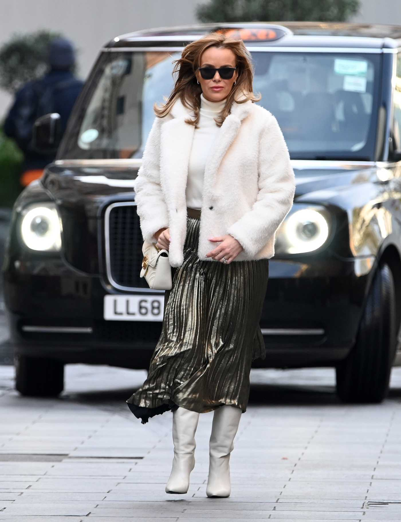 Amanda Holden in a Short White Fur Coat Arrives at the Global Radio Studios in London 12/16/2020