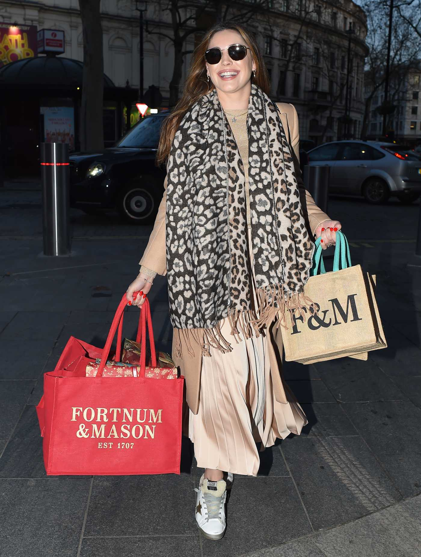 Kelly Brook in a Beige Coat with Christmas Gifts Arrives at the Global Radio in London 12/17/2020