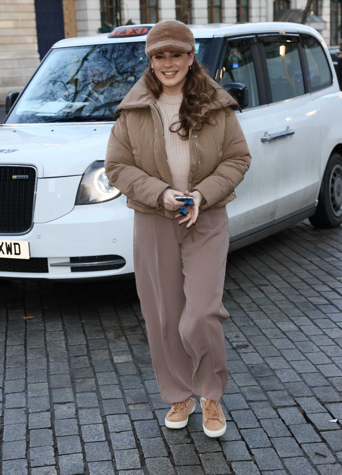 Kelly Brook in a Beige Puffer Jacket Arrives at the Heart Radio in London 01/25/2021