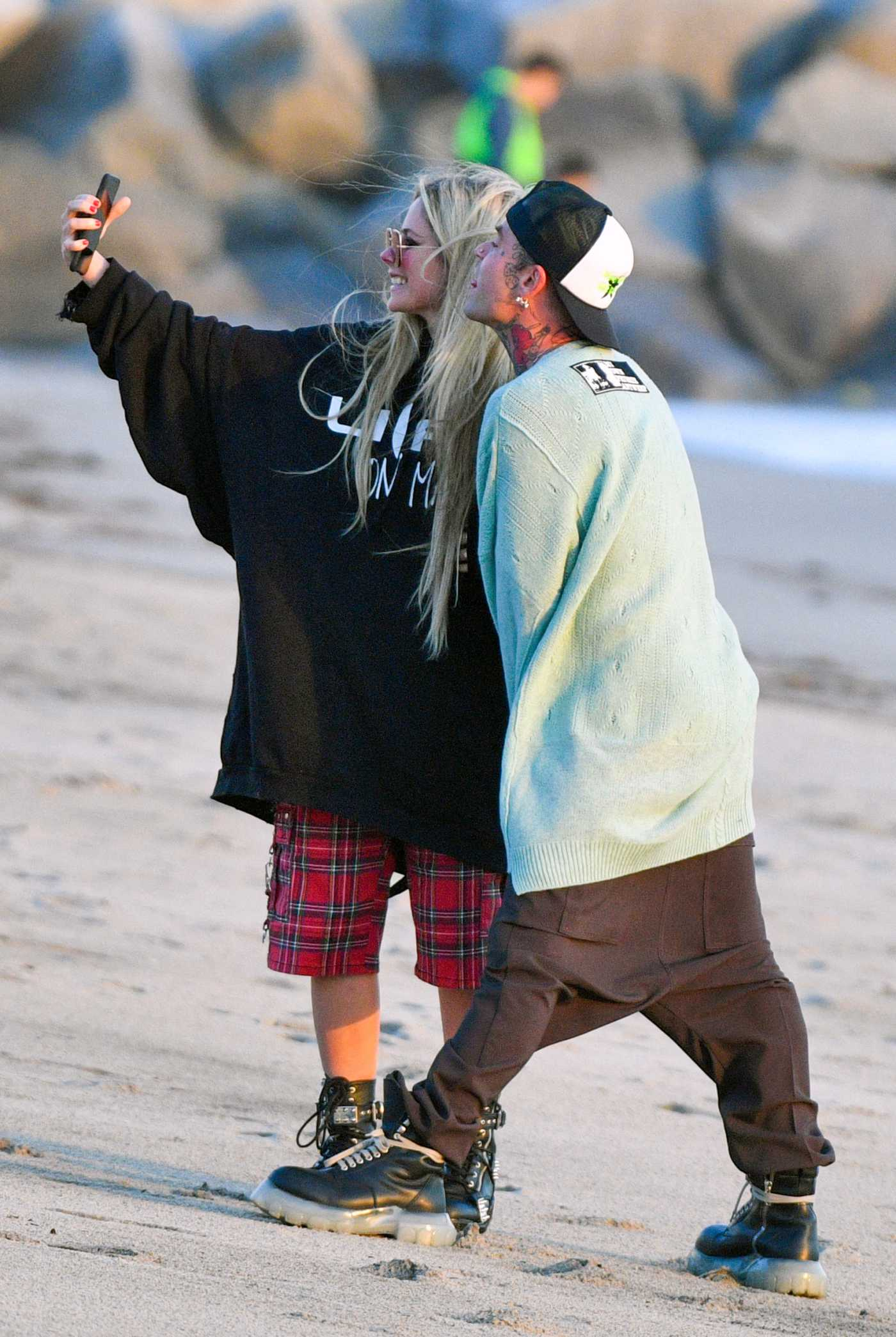 Avril Lavigne in Oversized Black Sweatshirt Was Seen Out with Mod Sun on the Beach in Santa Monica 03/10/2021