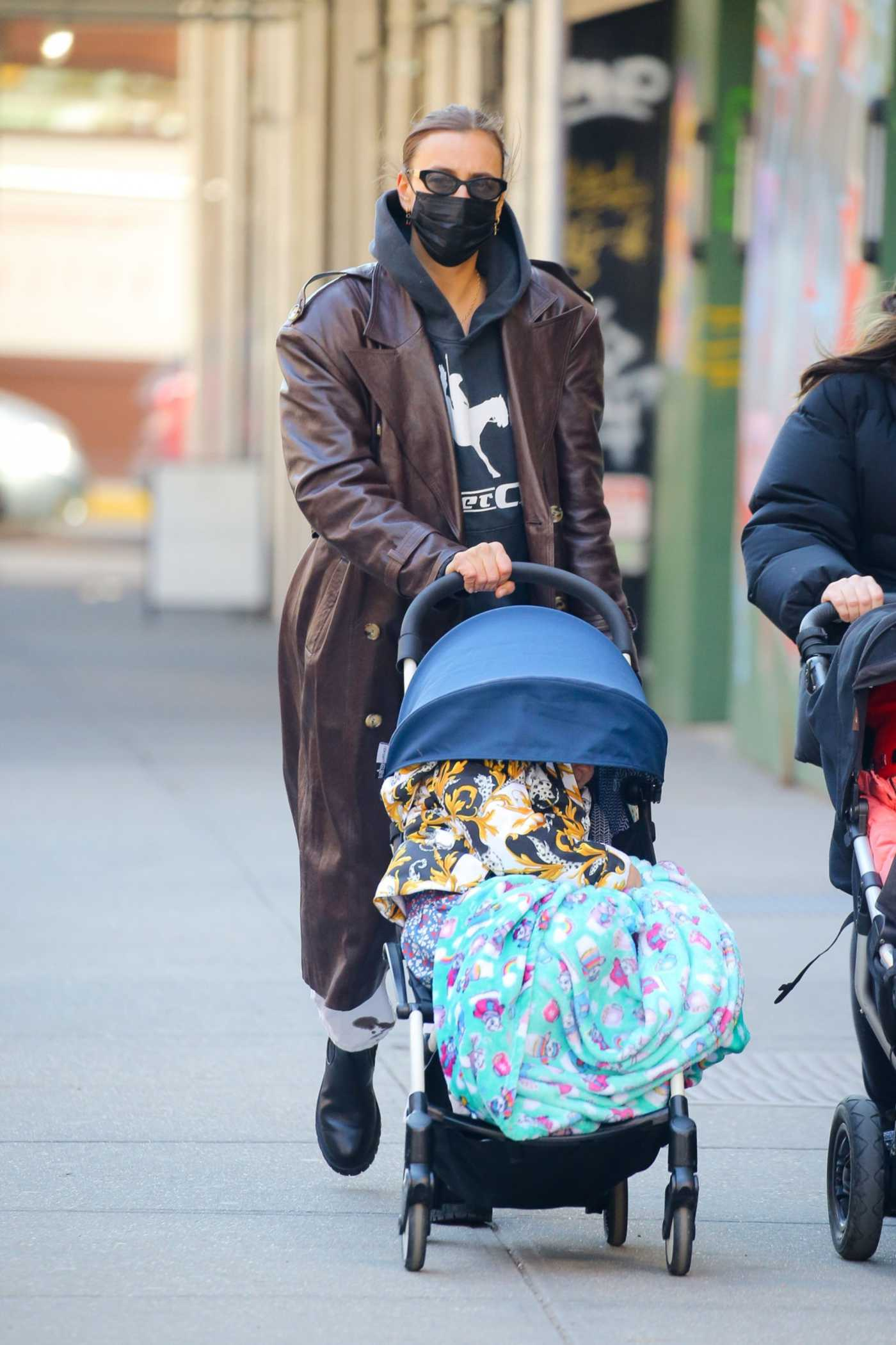 Irina Shayk in a Brown Leather Coat Takes a Stroll with Her Daughter through the West Village in New York City 03/08/2021