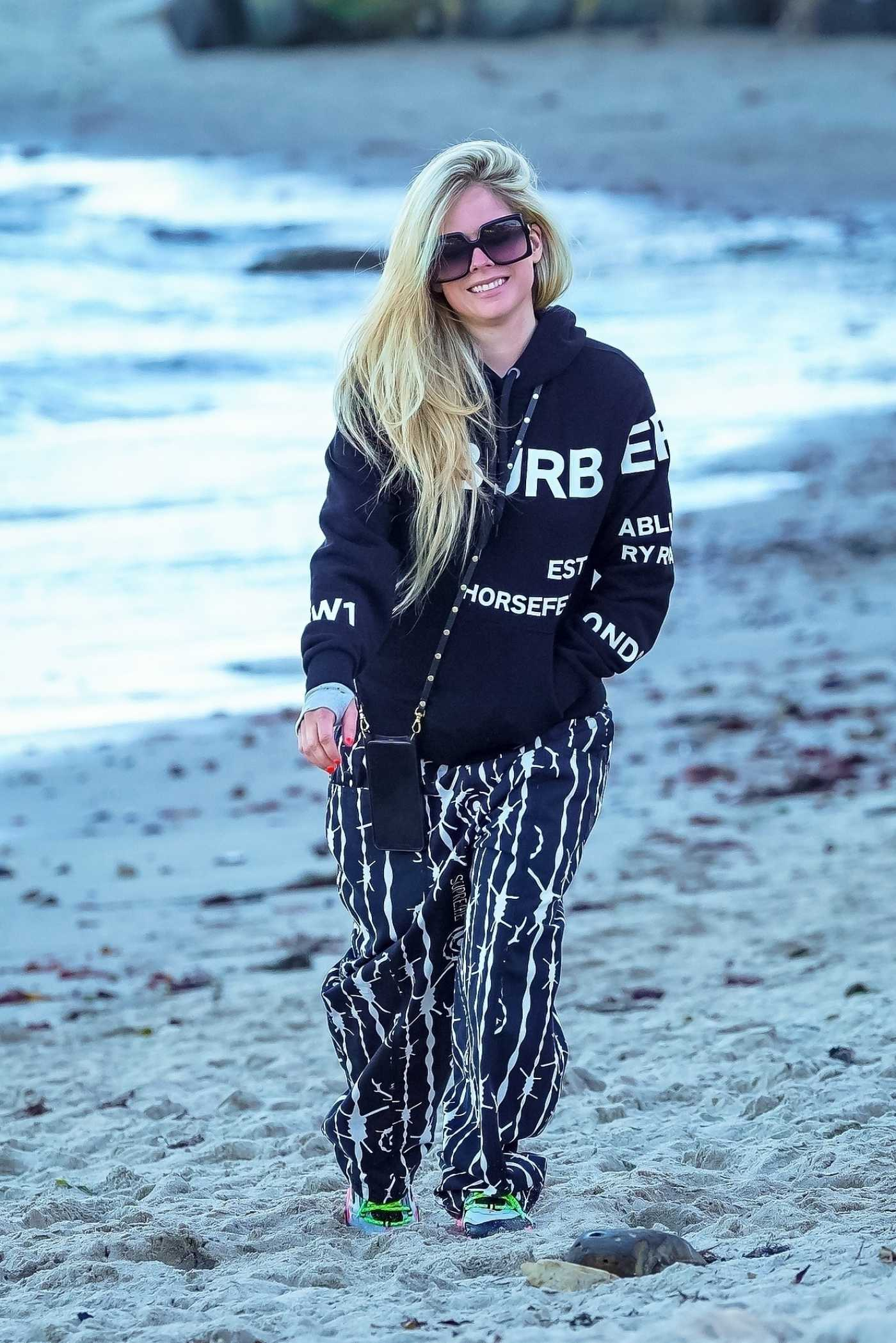 Avril Lavigne in a Black Hoodie Was Seen Out with Mod Sun on the Beach in Malibu 04/28/2021