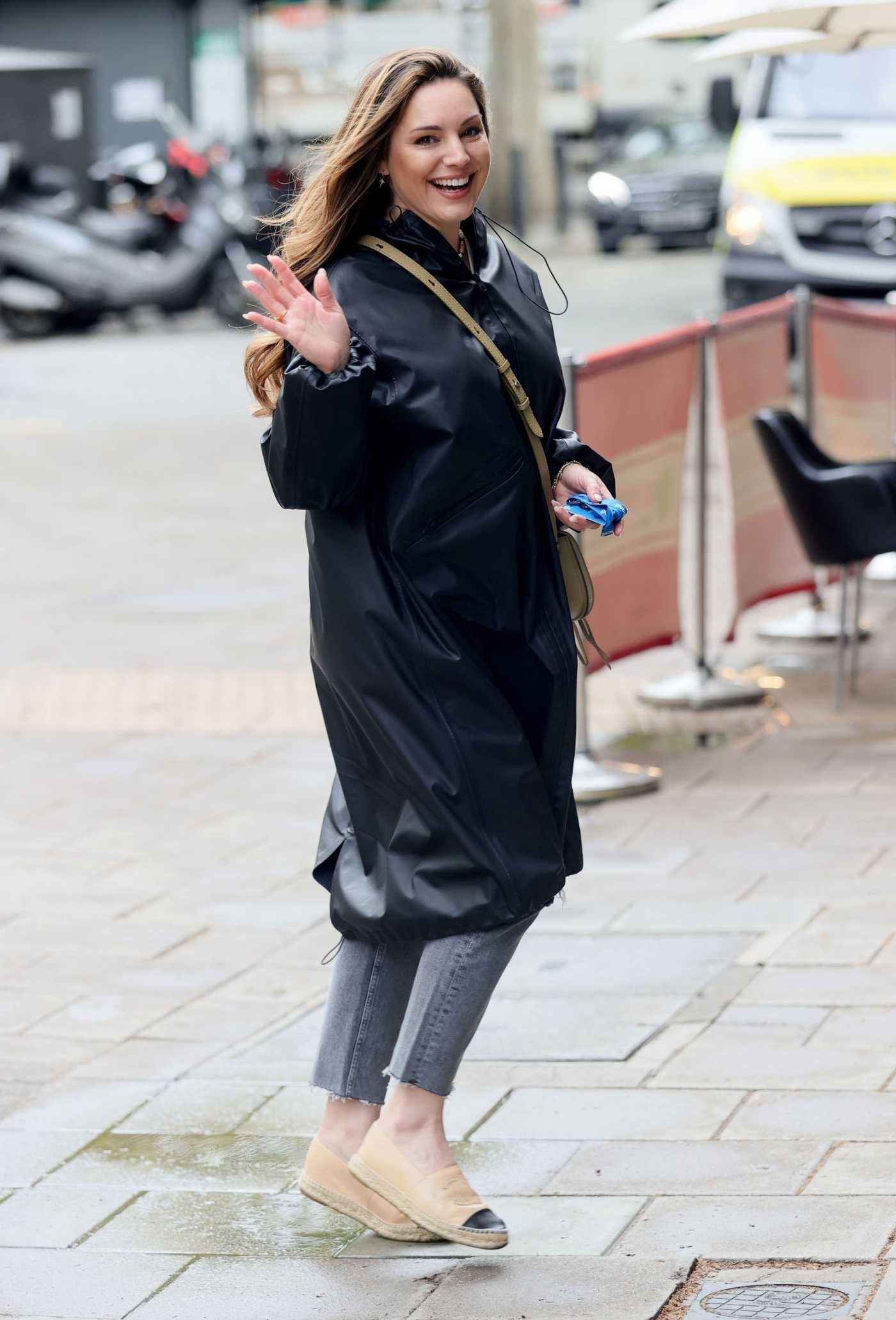 Kelly Brook in a Black Raincoat Arrives at the Heart Radio Studios in London 05/13/2021