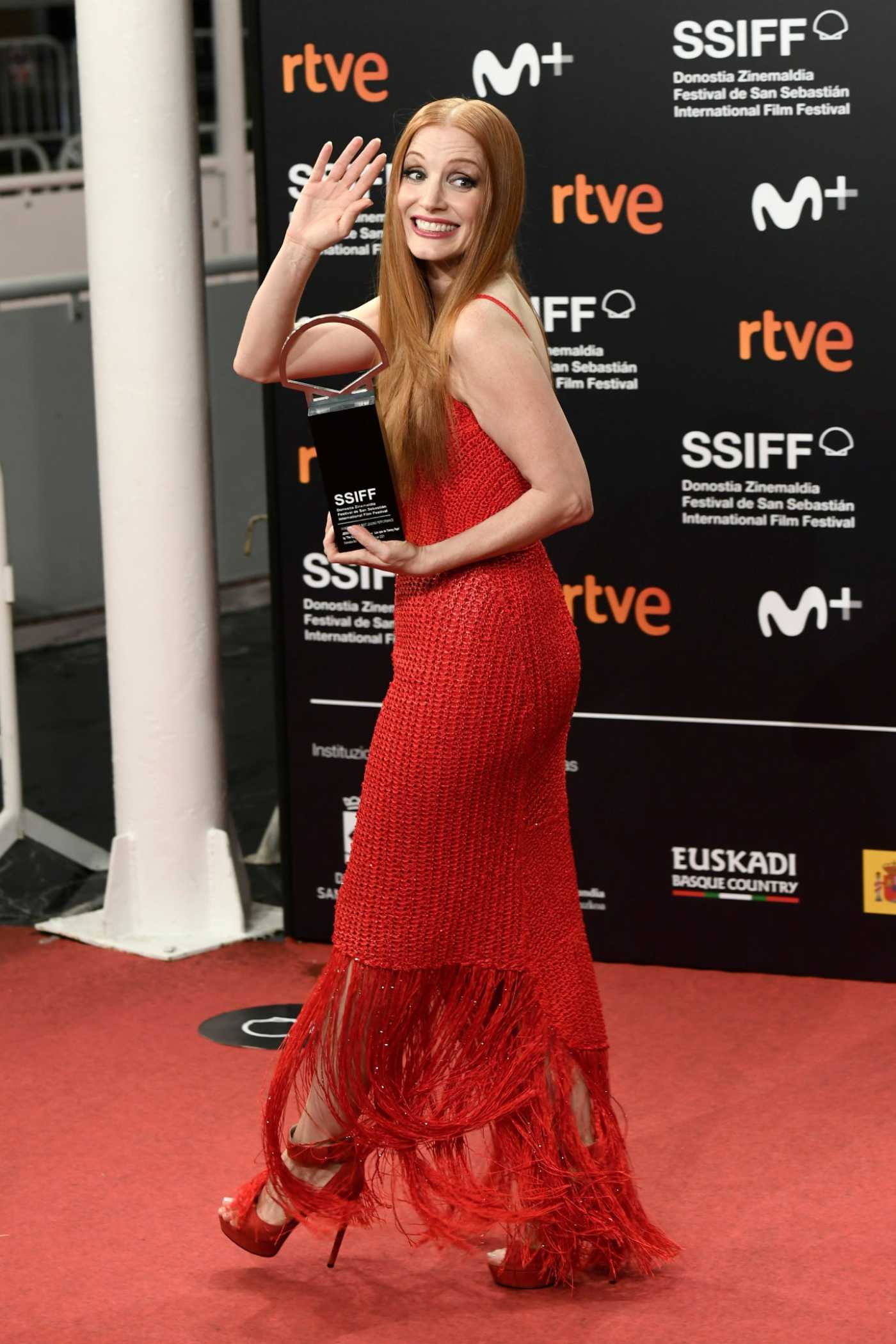 Jessica Chastain in a Red Dress Holds the Silver Shell for Best Leading Performance Award at the Kursaal in San Sebastian 09/25/2021