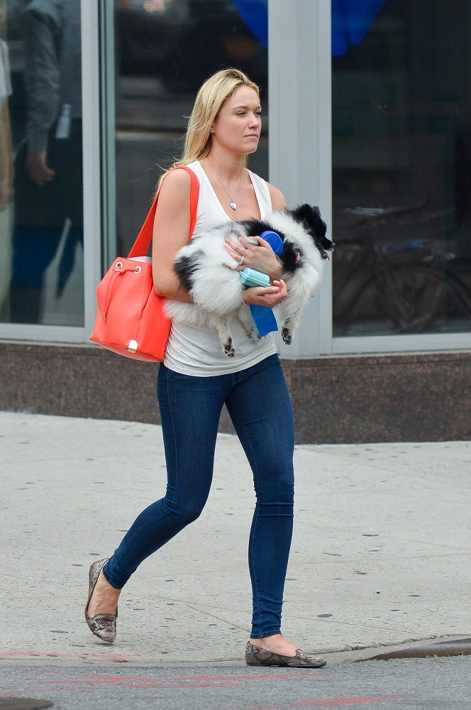 Katrina Bowden carries her dog while walking in the East Village